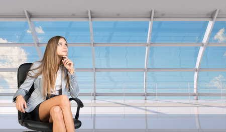 Thinking businesswoman sitting in chair with crossed legs and looking up
