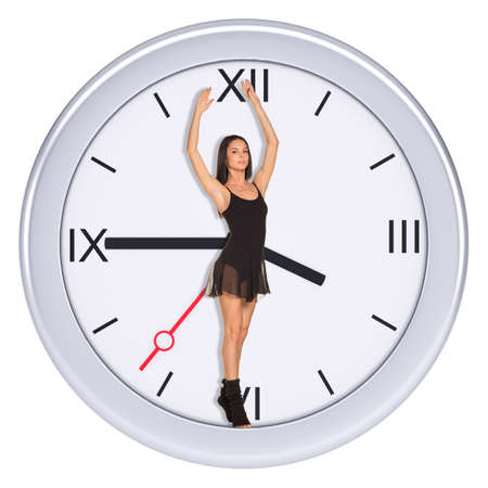 on tiptoes: Young woman standing in center of clock on isolated white background Stock Photo