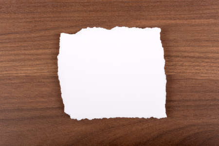 uneven edge: White piece of paper on brown wood table