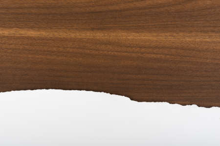 uneven edge: Piece of paper on brown wood table, close-up view