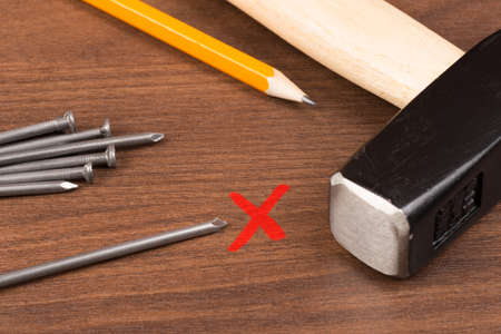 red cross: Hammer with pencil and red cross, nails on brown wood table, close-up view
