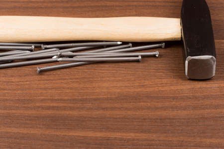 criss: Hammer and nails on brown wood table, front view Stock Photo