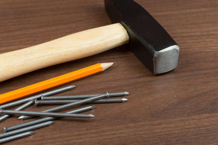 criss: Hammer with pencil and scattering nails on brown wood table, close-up view Stock Photo