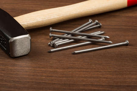 criss cross: Hammer with red handle, nails on brown wood table, close-up view