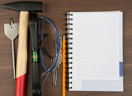 criss: Different working tools with note pad and pencil on brown wood table, close-up view
