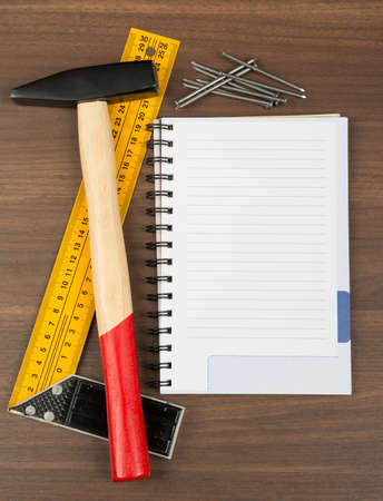 criss cross: Hammer with ruler, scattering nails and note pad on brown wood table, top view
