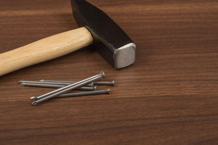 criss cross: Hammer with pile of nails on brown wood table, front view