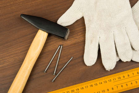 criss cross: Hammer with protective gloves, ruler and nails on brown wood table, close-up view