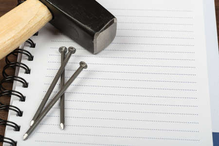 criss cross: Hammer with three nails and note pad on brown wood table, top view