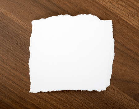uneven edge: White blank piece of paper with uneven edges on brown wood table