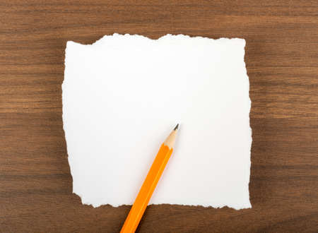 uneven edge: White blank piece of paper with pencil on brown wood table