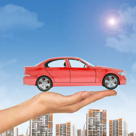 tailpipe: Red car above businesswomans hand with cityscape on blue sky background
