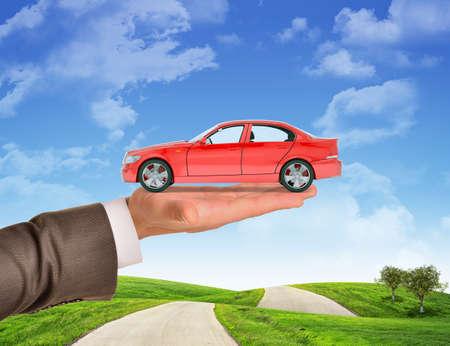 mano derecha: Coche en businessmans mano derecha sobre fondo de cielo azul y la hierba verde Foto de archivo