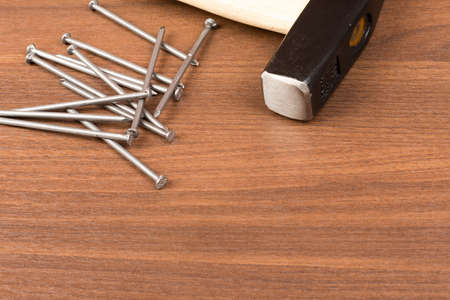 criss: Hammer and scattering nails on brown wood table, close-up view