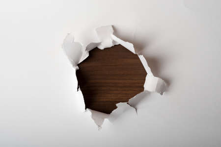 uneven edge: White blank piece of paper with brown wood hole in center, close-up view Stock Photo
