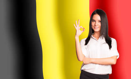 belgium flag: Smiling woman showing ok on Belgium flag background
