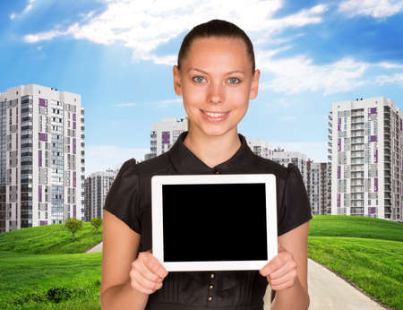 businesslady: Businesslady holding tablet and cityscape under blue sky with road Stock Photo