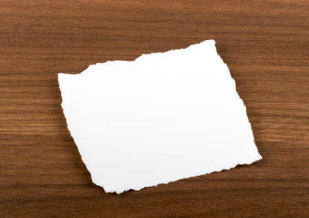 uneven edge: Blank piece of paper on brown wood table Foto de archivo