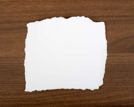 uneven edge: White blank piece of paper with uneven edges on brown wood table, yop view