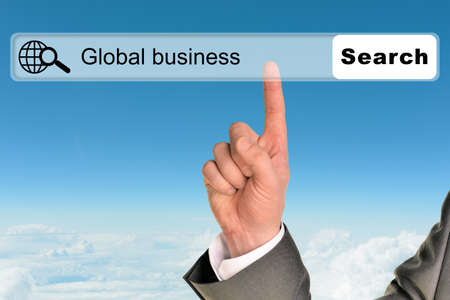 browser business: Businessmans hand on blue sky background with words global business in browser