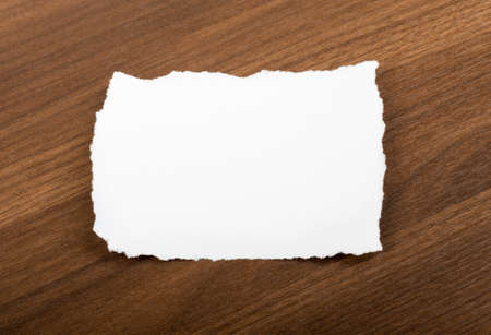 uneven edge: White blank piece of paper on brown wood table Stock Photo