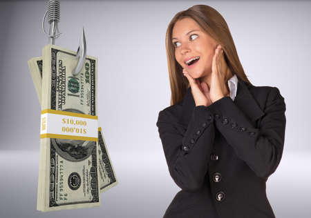 fishhook: Businesswoman in suprise looking at bundle of money on fish-hook on isolated grey background