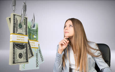suprise: Businesswoman in suprise sitting in chair and looking at bundles of money on fish-hooks on isolated grey background Stock Photo