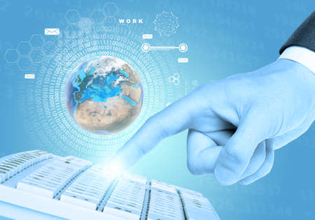 connected world: Businessmans finger touching keyboard on abstract blue background. Elements of this image furnished by NASA