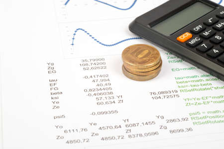 graphical: Documents with graphical charts and numbers, calculator and coins Stock Photo