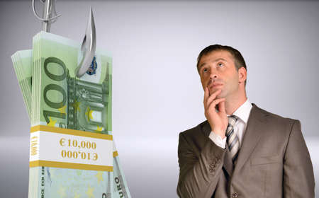 fishhook: Thoughtful businessman looking up with bundle of money on fish-hook on isolated grey background Stock Photo