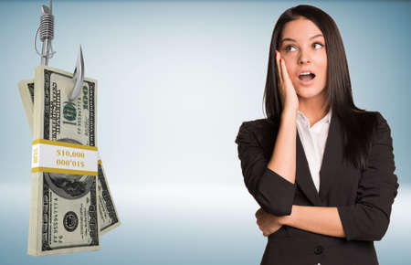 suprise: Businesslady in suprise with open mouth and bundle of money on fish-hook on isolated grey background Stock Photo