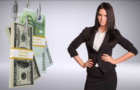 Serious business lady looking at camera and bundles of money on fish-hooks on isolated grey background