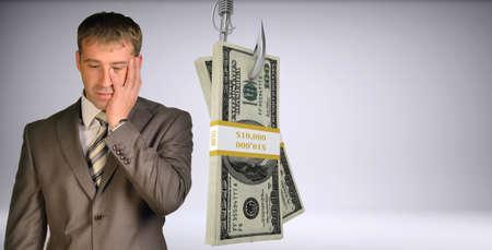 灰色背景: 孤立した灰色の背景に魚のフックにお金の束を見下ろし悲しい実業家