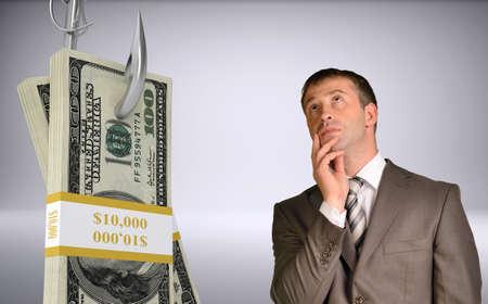 fishhook: Thinking businessman looking up with bundle of money on fish-hook on isolated grey background