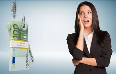 suprise: Young woman in suprise with open mouth and bundle of money on fish-hook on isolated grey background