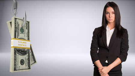 fishhook: Sad businesslady looking at camera and bundle of money on fish-hook on isolated grey background Stock Photo