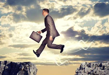 abyss: Businessman with suitcase jumping over abyss on nature background Stock Photo