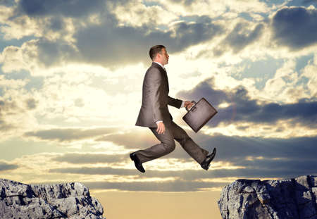 abyss: Businessman with suitcase hopping over abyss on nature background