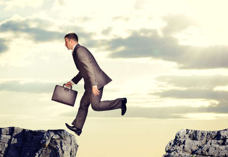 abyss: Businessman with suitcase jumped over abyss on nature background