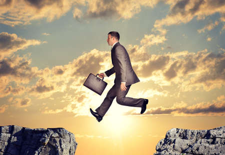 abyss: Entrepreneur with suitcase jumping over abyss on nature background Stock Photo
