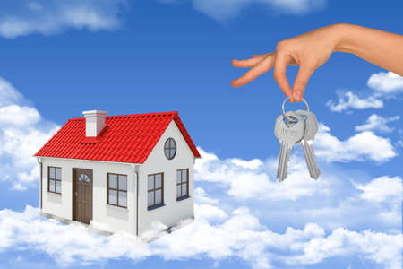 coziness: House with hand holding keys in blue sky with clouds Stock Photo