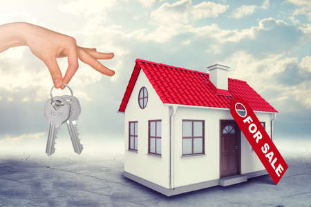coziness: House for sale with hand holding keys on blue sky background
