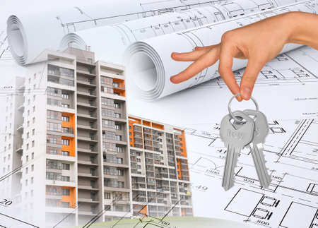 key: Buildings with hand holding keys on abstract background with drafts Stock Photo