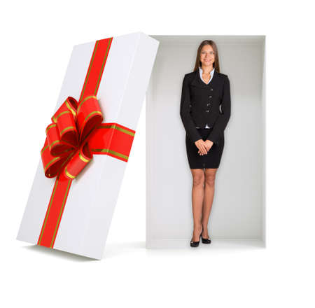 giftware: Businesswoman looking at camera in gift box with ribbon on isolated white background