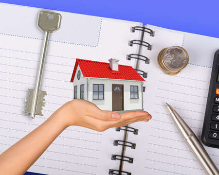 hand holding house: Humans hand holding house with key, pen and notebook