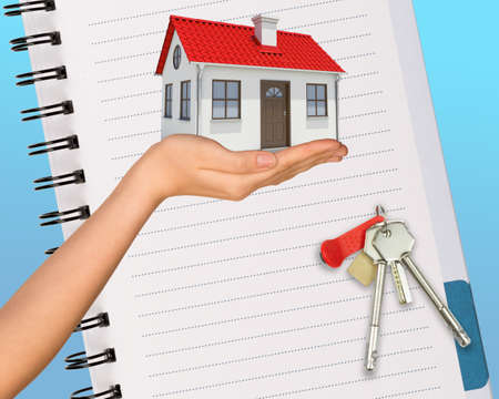 and real estate: Humans hand holding house with keys and open notebook