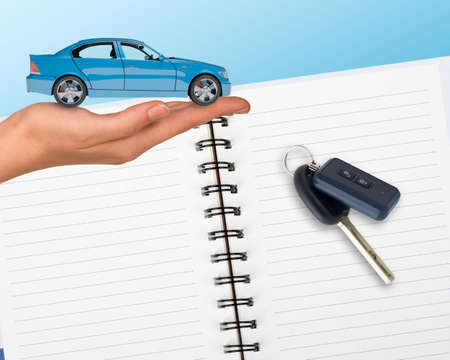 tailpipe: Humans hand holding car with open notebook