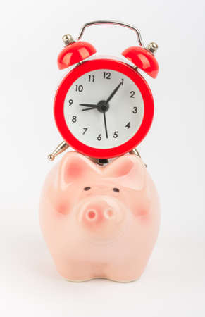 solated: Red alarm clock on piggy bank solated white background Stock Photo