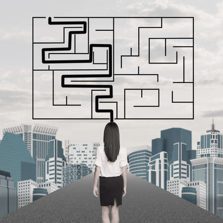 businesslady: Businesslady with labyrinth and cityscape background, back view