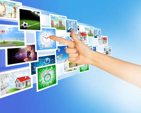 holographic: Arm pointing at holographic pictures on abstract background Stock Photo